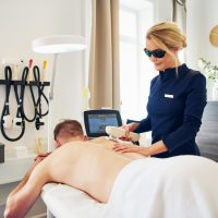 Young female beautician wearing protective glasses performing laser hair removal on the back of a man lying on a table in a beauty clinic