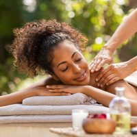 Beautiful woman receiving back massage at resort spa. Happy african american girl receiving back massage outdoor. Relaxed girl lying on spa bed with eyes closed while getting a beauty treatment.