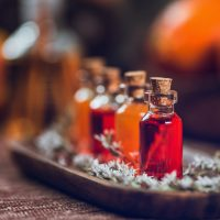 Bottles filled with red and orange essential oils on wooden board. Aromatherapy relax concept