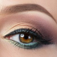 Closeup view of brown female eye with evening makeup. Colourful smokey eyes with black eyeliner. Studio shot