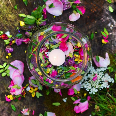 Aromatherapy bowl for relaxing herbal bath with beautiful flower petals and leaves.