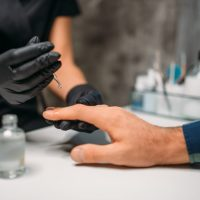 Beautician in black gloves polishing nails to male client, top view, men manicure in salon. Manicurist doing hands care procedure