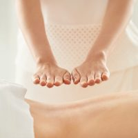 Hands of woman doing reiki healing treatment on female patient